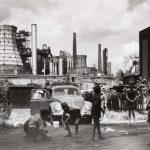 Rudolf Holtappel (Münster, Germania, 1923 – Duisburg, Germania, 2013) , Duisburg Bruckhausen, Ebertstrasse con stabilimento metallurgico August Thyssen, 1959; Estate of the Artist, Stampa ai sali d'argento, 29,1 × 37,8 cm